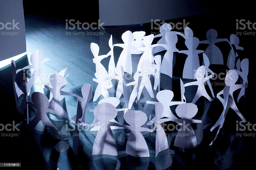 Crowd of paper people keeping for hands royalty-free stock photo