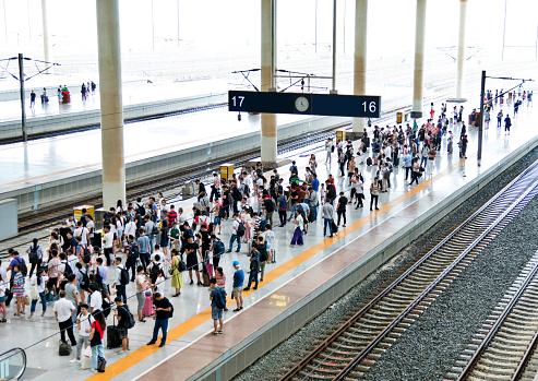 Crowd of passengers waiting on station platform.