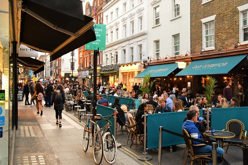 London, United Kingdom - September 11 2020: Social distancing outdoor street seating at bars and restaurants on Old Compton Street, Soho with crowd of people