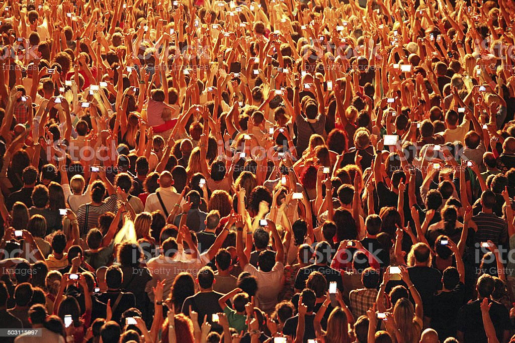 Crowd of people at concert with hands raised and smartphones stock photo