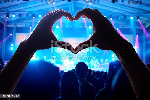 a crowd of people at during a concert with a heart shaped hand shadowa crowd of people at during a concert with a heart shaped hand shadow