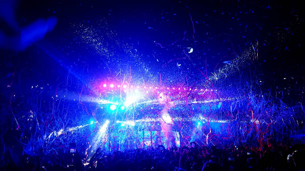 Crowd of people being showered in streamers and confetti at a rock concert stock photo