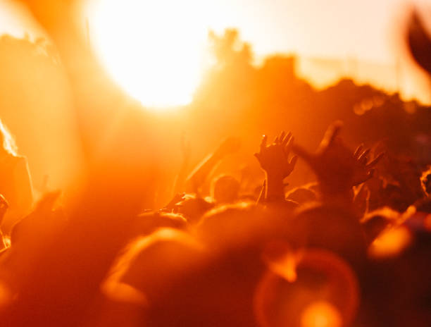 Crowd of people cheering at a music festival at sunset stock photo