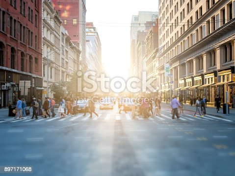 813211754 istock photo Crowd of people crossing street in New York City 897171068