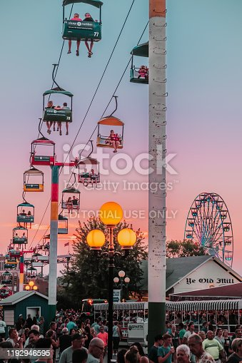 Des Moines, Iowa / United States - August 10, 2018: Sunset scene of crowds of people, a ferris wheel, Ye Old Mill and the Sky Glider at the Iowa State Fair, Des Moines, Iowa, USA.