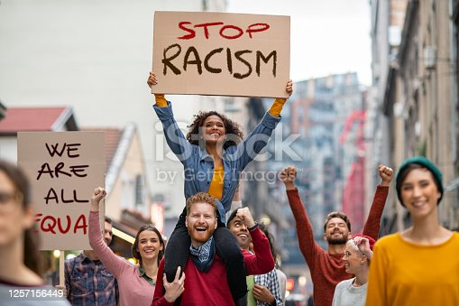 Young group of men and smiling women marching through the city during an anti Racism protest. Group of multiethnic people on city street holding cardboard against racism during a protest. People protesting on road for equality and justice.