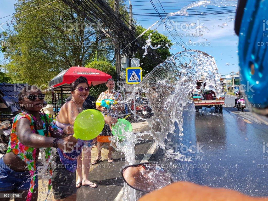 Crowd of people pour water on motorbike driver celebrate traditional Thai New Year - Songkran Festival zbiór zdjęć royalty-free