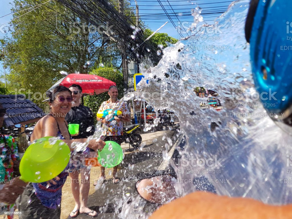 Crowd of people pour water on motorbike driver celebrate traditional Thai New Year - Songkran Festival zbiór zdjęć royalty-free