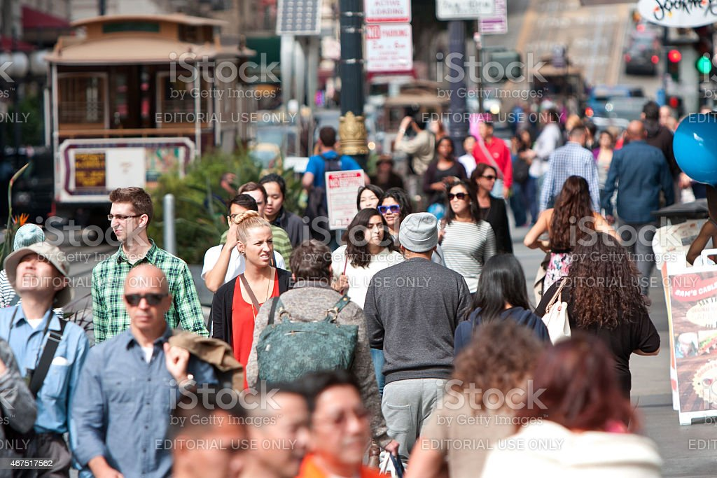 Crowd Of People Walk Among Trolley Cars In San Francisco stock photo