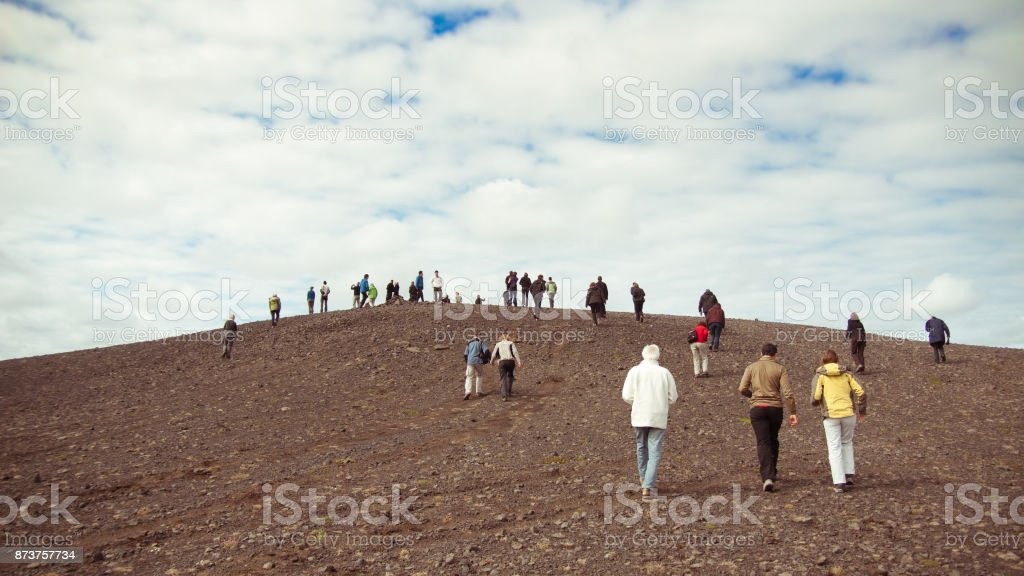 Crowd of people walk up a hill stock photo