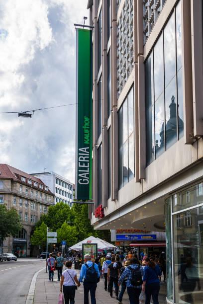 menschenmassen am rotenbühlplatz in der stuttgarter innenstadt unter riesigem banner der galeria kaufhof-lagerhalle - rewe germany stock-fotos und bilder
