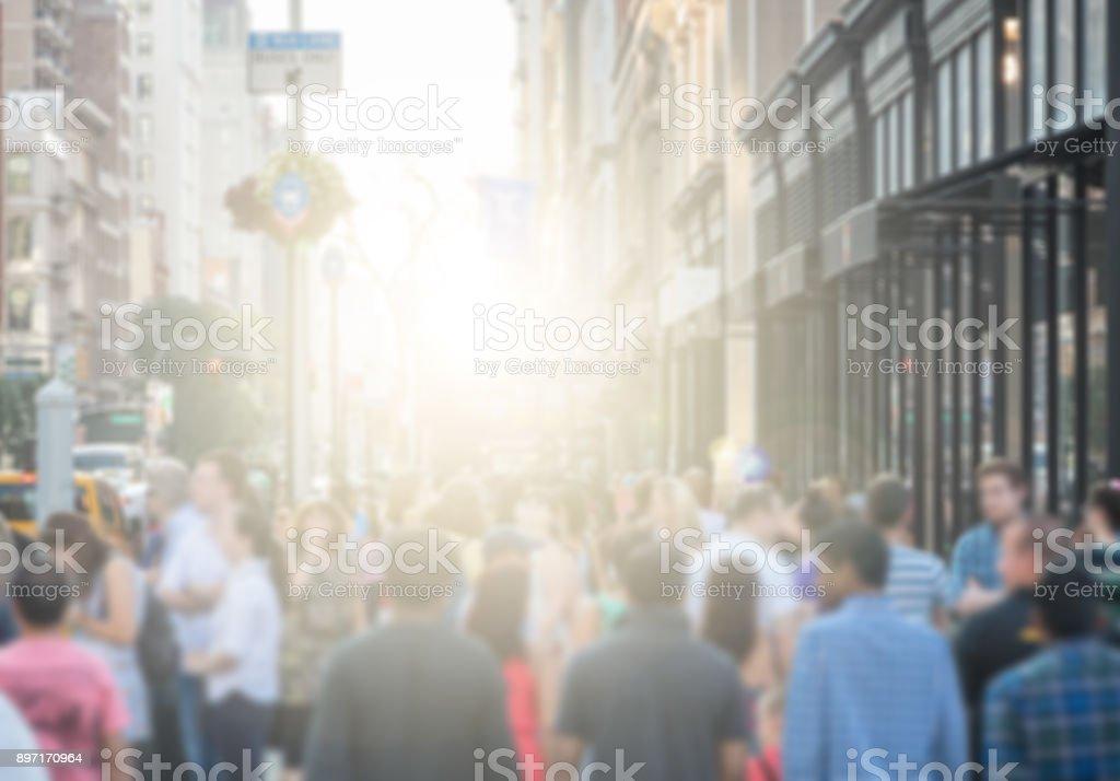 Crowd of people walking down a busy street sidewalk in downtown...
