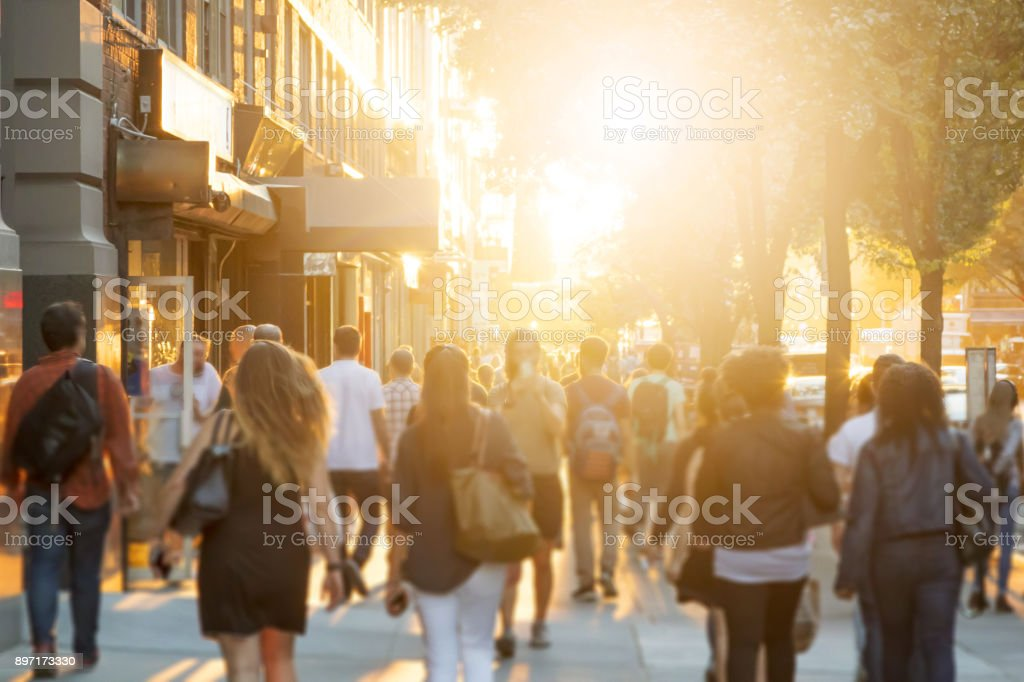 Crowd of people walking down sidewalk in Manhattan, New York City stock photo