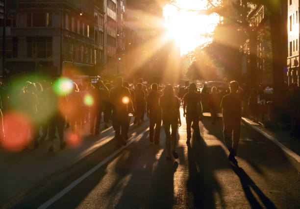 Crowd of people walking down the street into the bright light of sunset in New York City Crowd of people walking down the street into the bright light of sunset in New York City NYC marching stock pictures, royalty-free photos & images