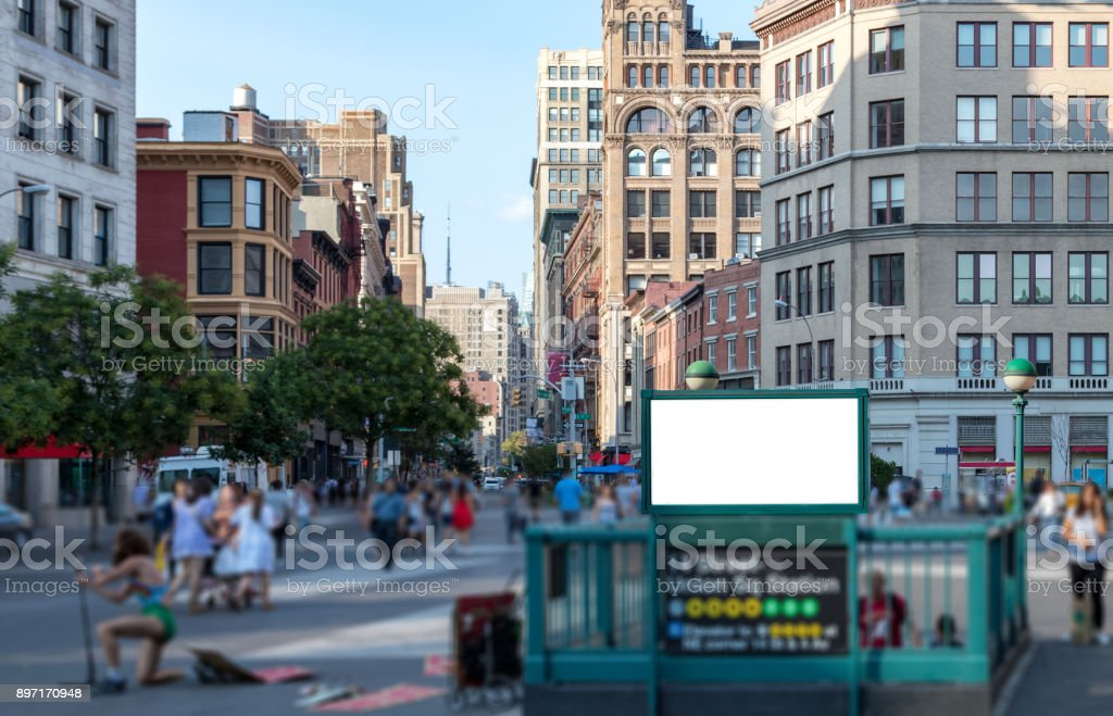 Crowd of people walking in Union Square Park in Manhattan, New York City NYC with a blank billboard sign and glowing sunlight in the background stock photo