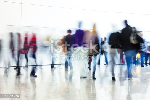 crowd of people walking down modern interior, blurred motionClick here to view more related images: