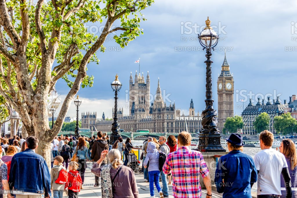 Crowd of people walking on the southern bank of the River Thames, London stock photo
