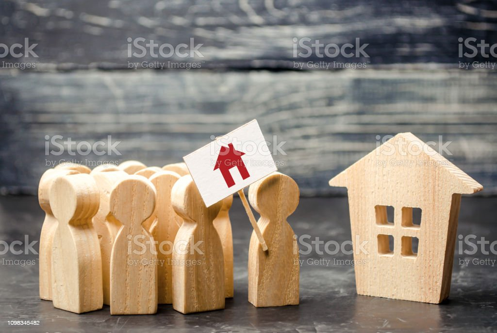 A crowd of people with a poster standing near the house. The concept of finding housing, a new home. High demand for housing, affordable loans and mortgages. Refugees seek asylum. meeting place stock photo