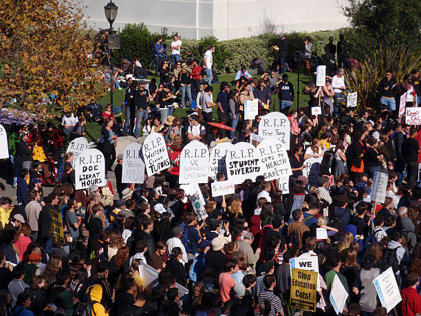 crowd of protesters hold signs and rally tuition increases stock photo