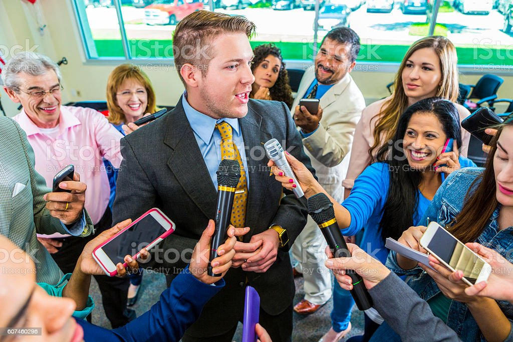 Crowd of reporters interview mid adult male politician stock photo