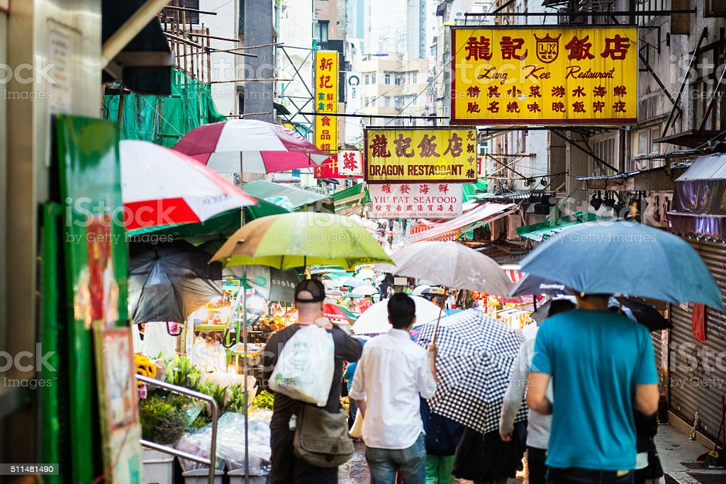 Crowd of Shoppers Walking Through Outdoor Market, Hong Kong, China Hong Kong iStockalypse.  Shoppers with umbrellas walk through a busy outdoor food market and restaurant area on a rainy day in Sheung Wan District, Hong Kong, China Adult Stock Photo