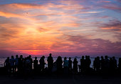 Color image depicting a crowd of back lit, silhouetted and unrecognisable people watching either a sunset or a sunrise on the shoreline of the sea. The sky is a beautiful tapestry of blue, orange and pink, and the crowds of people are watching the colors of the sky intently, while some are taking photographs using their smart phones. Lots of room for copy space.