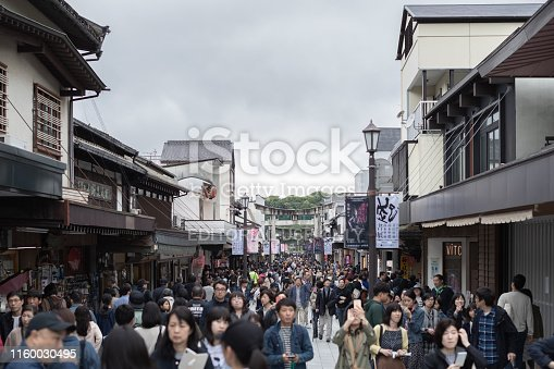 Fukuoka, Japan - April 30, 2019 : A crowd of tourists and shopping street with entrance stone torii gate at Dazaifu Tenmangu Shrine.
