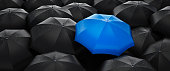 Crowd of black Umbrellas with one unique blue outstanding umbrella