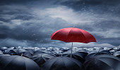Crowd of black Umbrellas with one unique red outstanding umbrella in the storm