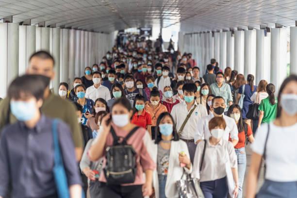 コロナウイルスの流行を防ぐために外科用マスクを着用した認識できないビジネスマンの群衆 - 通勤 ストックフォトと画像