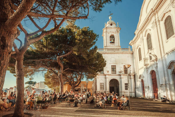 crowd of visitors of outdoor restaurant drinking and relaxing on terrace with beautiful city view - people lisbon imagens e fotografias de stock
