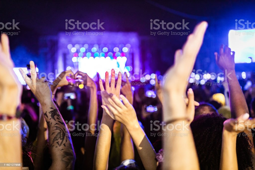 Large group of unrecognizable people\'s hands on a music festival.