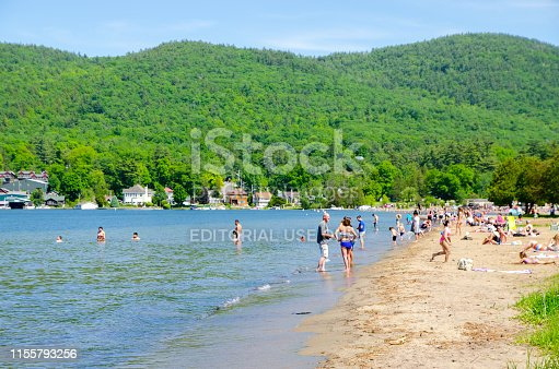 Crowd of swimmers on beach of Lake George (NY) during day of springtime