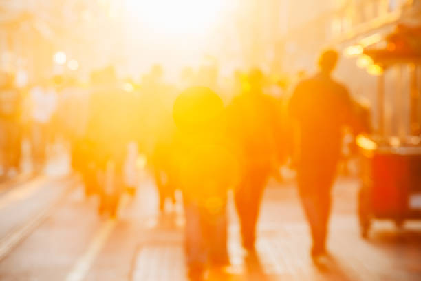 Crowd on blur street in bright lens flare stock photo