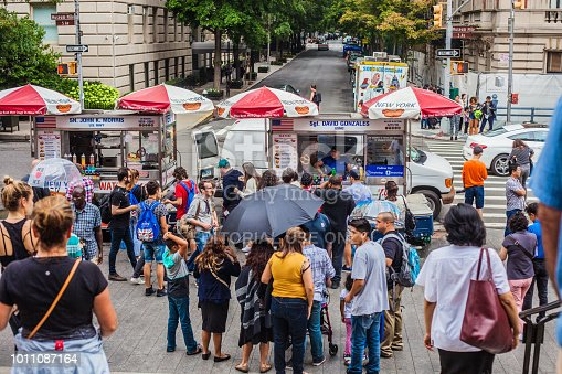 New York City, United States of America - July 25, 2018. A crowd gathers by hot dog trucks in front of New York's Metropolitan Museum of Art.