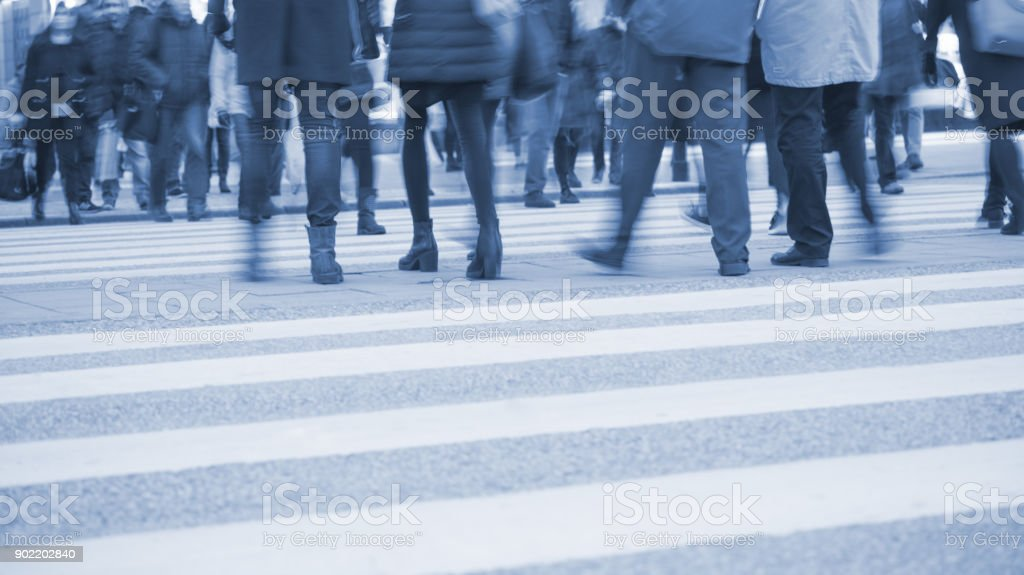 Zebra crossing with motion blurred young people crowd. Brightly lit...