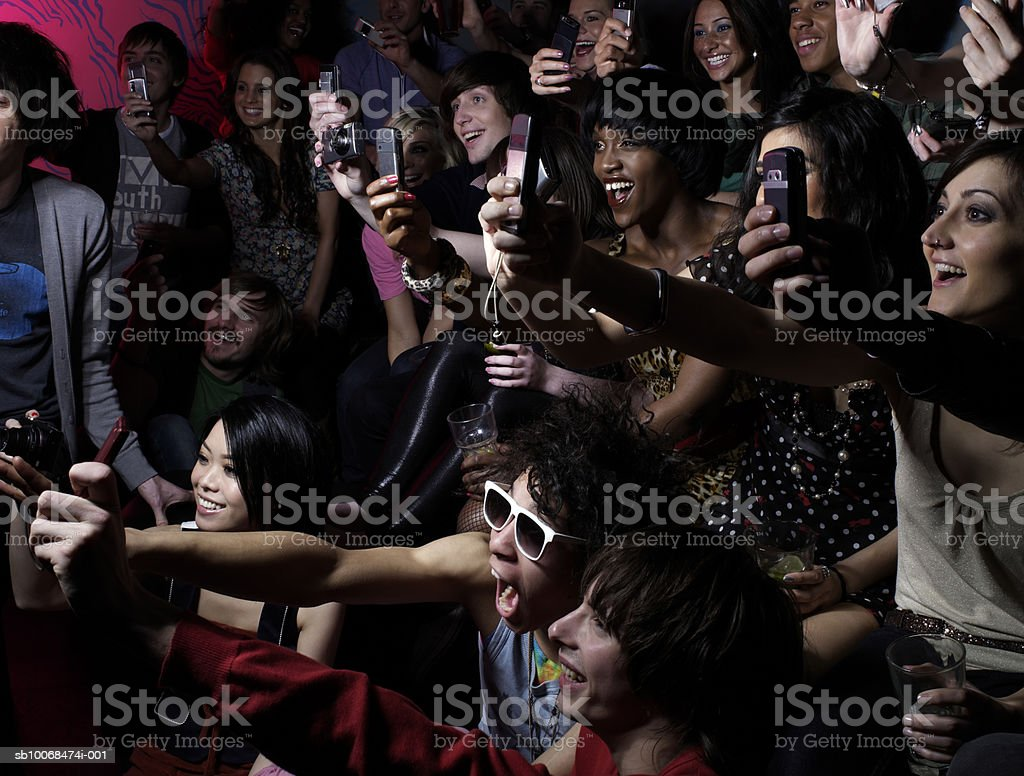 Crowd photographing using mobile phones at party royalty free stockfoto