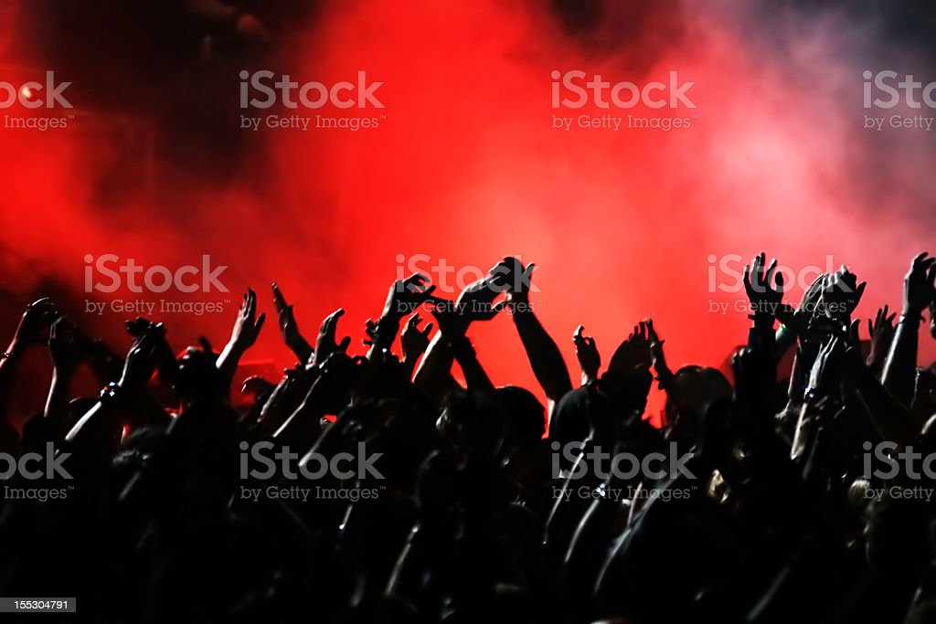 A crowd raising their arms and cheering at a concert royalty-free stock photo