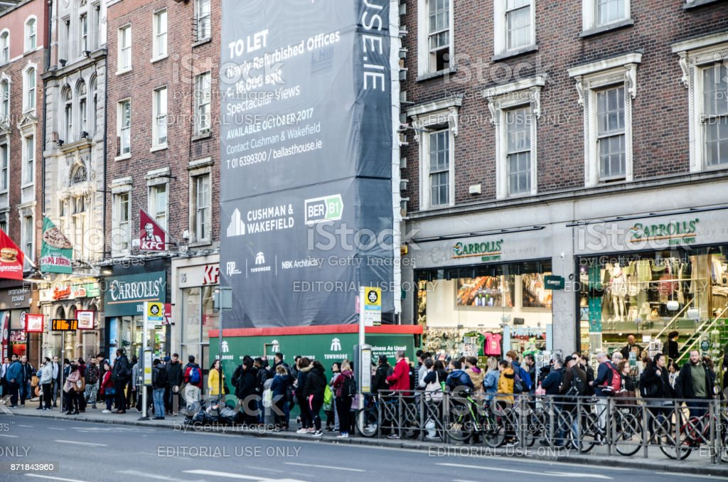 Crowd waiting for the bus on O'Connell street at the corner of Aston Quay  in Dublin Ireland during day of autumn stock photo