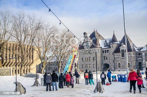 Crowd waiting in line for sliding at George V park, Downtown Quebec city  during a winter day Quebec armoury is in background
