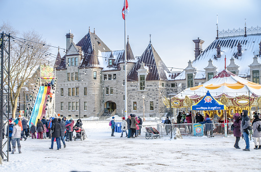 Crowd waiting in line for the carousel at George V park, Downtown Quebec city  during a winter day Quebec armoury is in background