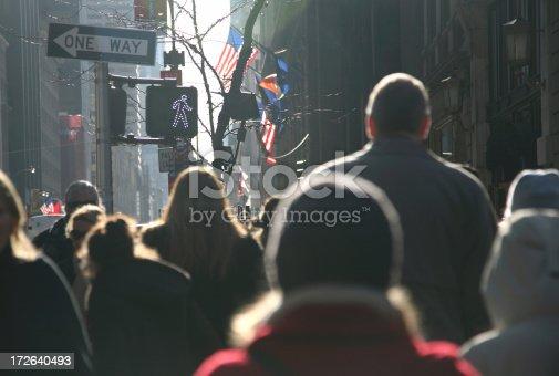Sun on pedestrians crossing a street in New York City.