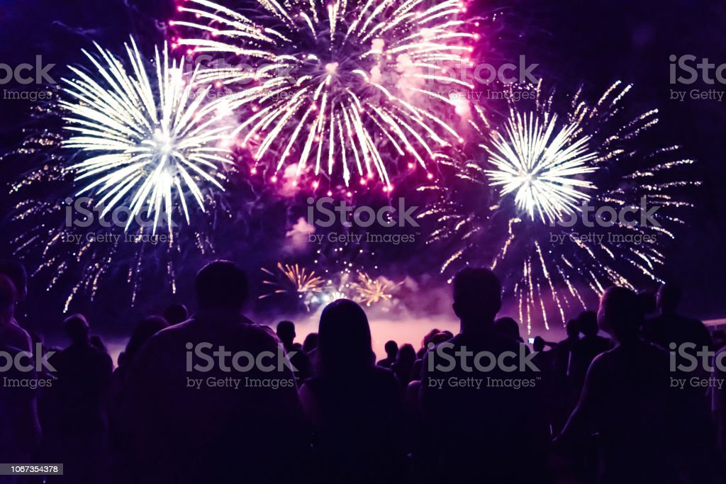 Crowd watching fireworks and celebrating new year eve Crowd watching fireworks and celebrating new year Anniversary Stock Photo