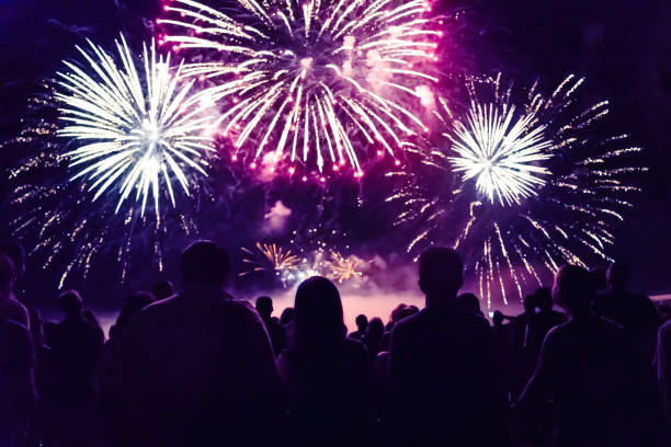 crowd watching fireworks and celebrating new year eve - fireworks stock pictures, royalty-free photos & images