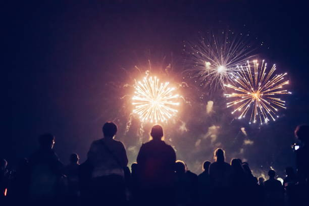 Crowd watching fireworks and celebrating new year eve stock photo