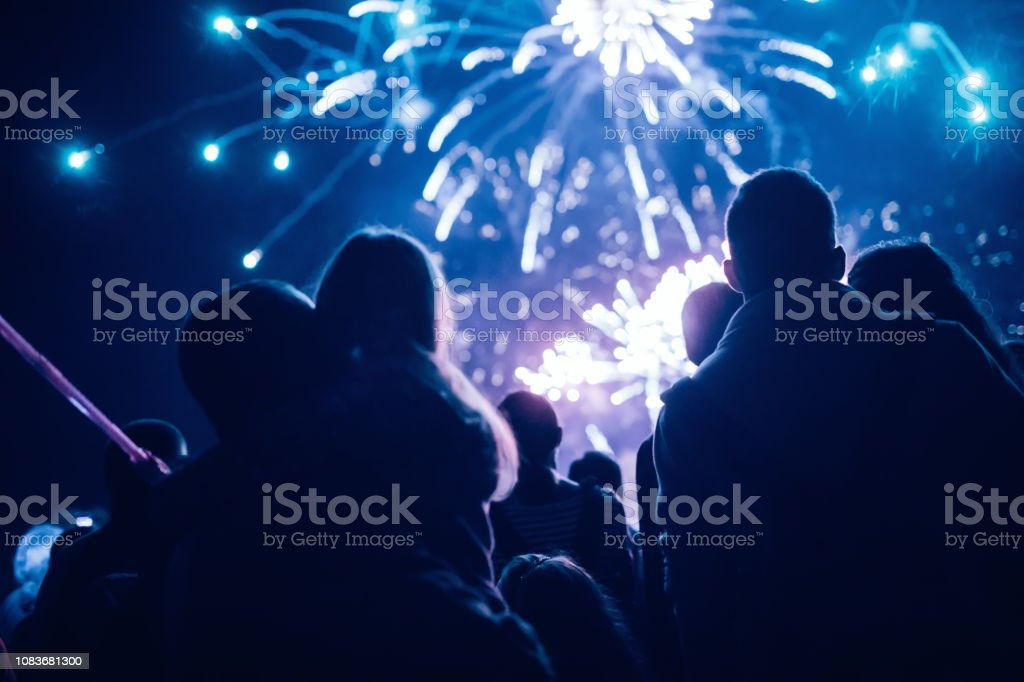 Crowd watching fireworks and celebrating new year eve Crowd watching fireworks and celebrating at night Anniversary Stock Photo