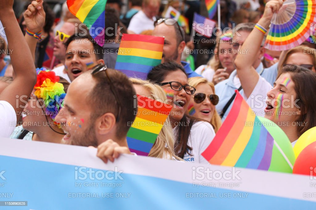 Crowd with Rainbow flags and banner at The annual Pride Parade LGBT....