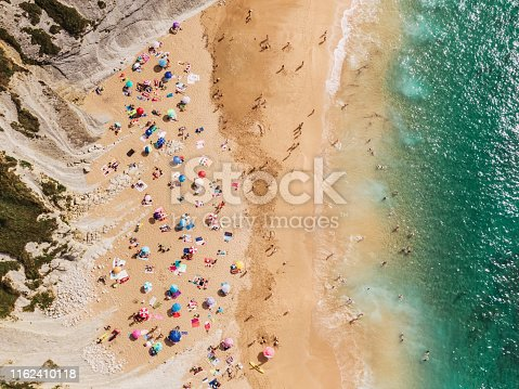 Aerial view of a beautiful beach with a large number of people and beach umbrellas