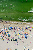 Aerial shot of a Baltic sea beach full of people. White sand beach and green Baltic sea. Shot taken in Kaliningrad region, Russia.