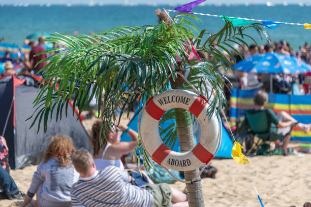 Crowded beach with a sign saying Welcome Aboard on a lifering stock photo